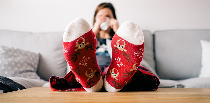 A lady drinking a hot drink with thick socks on.