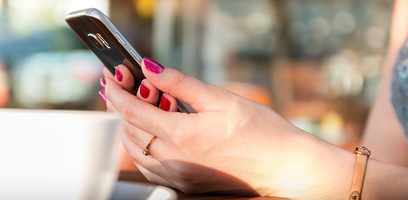 A woman with red nail varnish holding her mobile phone