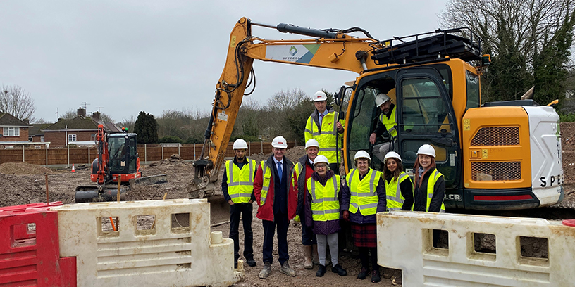 Members of our development panel next to a digger, at Queensmead construction site
